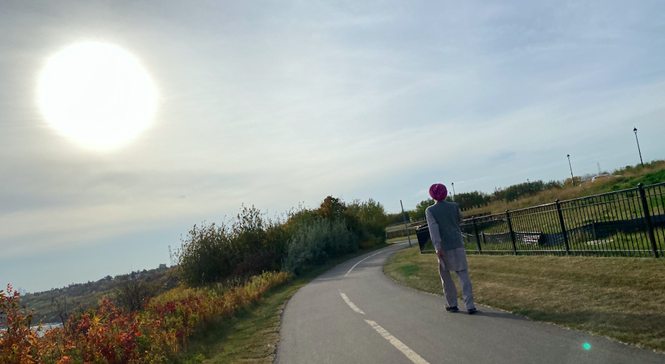 A man in a turban walking along the walking path surrounded by trees  and a bright glare of the sun in the sky