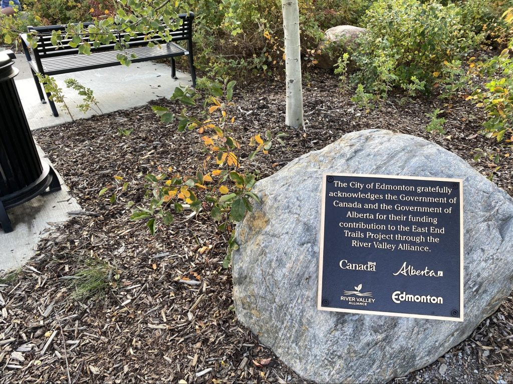 "A plaque sits on top of a rock that reads ""The City of Edmonton gratefully acknowledges the Government of Canada and the Government of Alberta for their funding contribution to the East End Trails Project through the River Valley Alliance."""